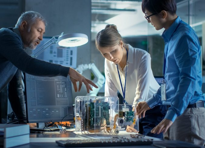 Team of Computer Engineers Lean on the Desk and Choose Printed Circuit Boards to Work with, Computer Shows Programming in Progress. In The Background Technologically Advanced Scientific Research Center.